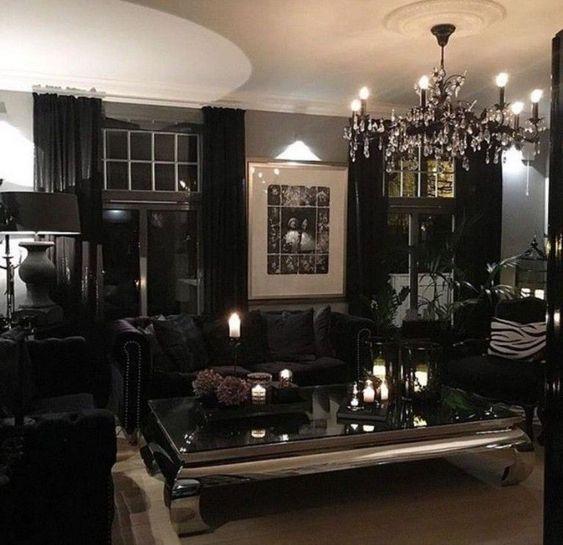 un salon glamour gothique moderne avec des murs gris, des rideaux et des meubles noirs, un lustre en cristal et des bougies