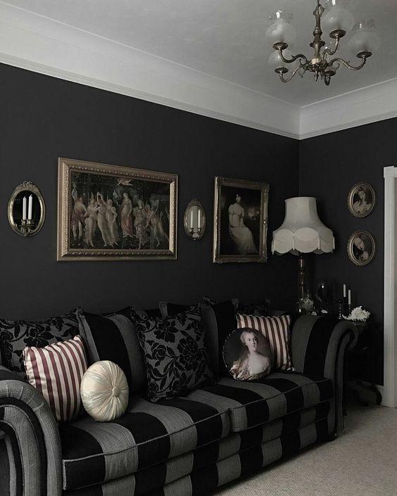 un salon gothique élégant avec des murs noirs, un canapé à rayures, des œuvres d'art, un lustre et des oreillers imprimés