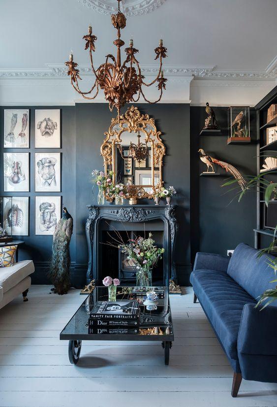 un salon gothique moderne avec des murs noirs, un canapé bleu et blanc, une cheminée, un lustre et un miroir raffinés, des œuvres d'art accrocheuses