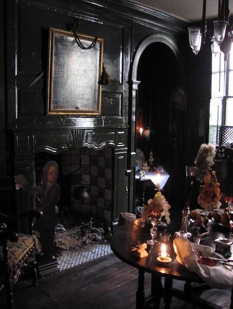 un élégant salon gothique avec des murs noirs, une cheminée, des œuvres d'art, un lustre et une table avec des cristaux et des fleurs