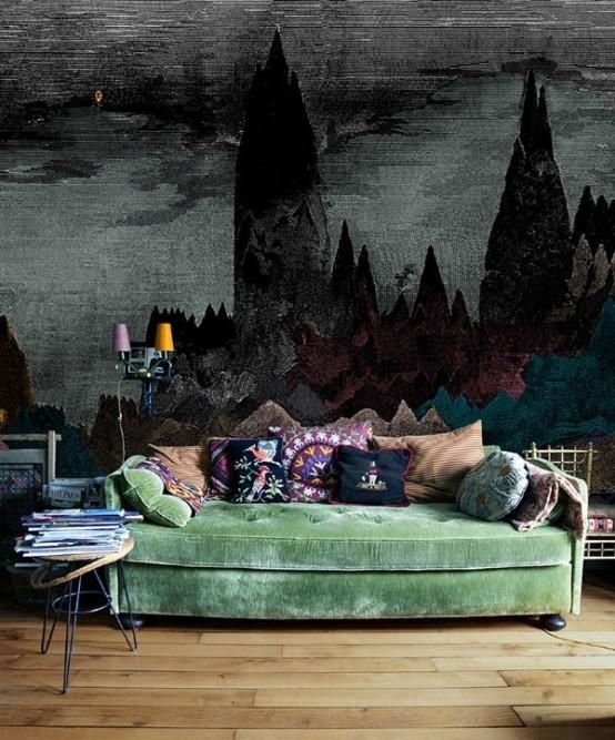 un salon gothique avec une touche de couleurs vives - un canapé vert avec des oreillers colorés et une fresque murale tendance