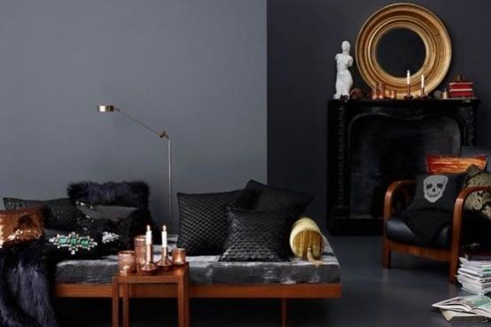 un salon gothique moderne avec des murs gris, un mur noir avec une cheminée, des bougies, un miroir dans un cadre doré, un canapé et des oreillers audacieux et noirs