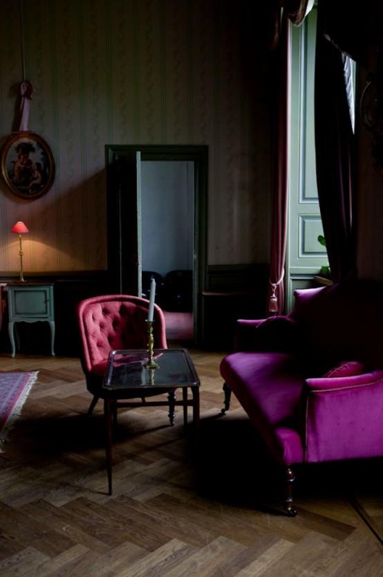un salon gothique moderne avec du papier peint imprimé, des murs lambrissés, des meubles aux tons bijoux, des touches d'œuvres d'art vertes et de mauvaise humeur