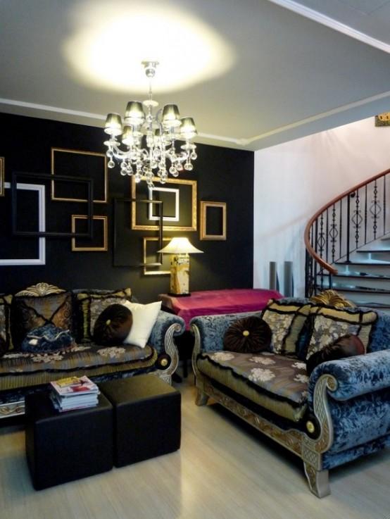 un salon gothique doux et raffiné avec un mur noir avec des cadres vides, un mobilier vintage exquis, un lustre en cristal et des poufs noirs