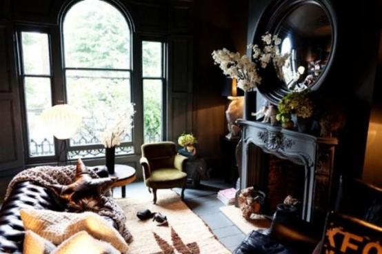 un salon gothique chic avec des murs noirs, une fenêtre aux formes accrocheuses, une cheminée noire et un miroir rond, une chaise verte et un canapé en cuir
