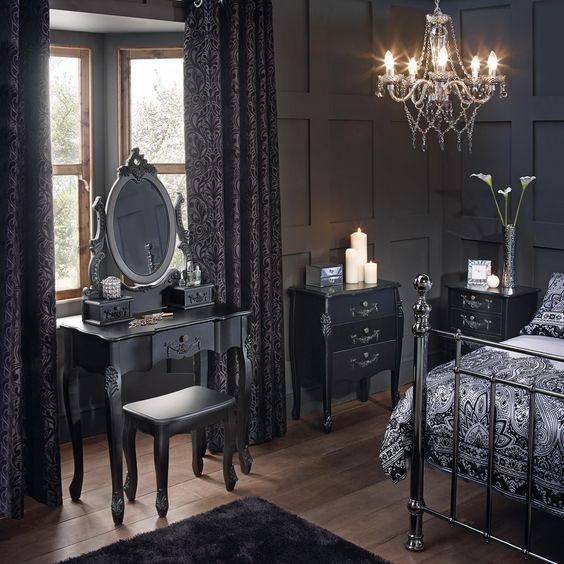 un espace gothique avec des boiseries gris graphite, un mobilier raffiné, un lit forgé, un lustre en cristal et des draps foncés