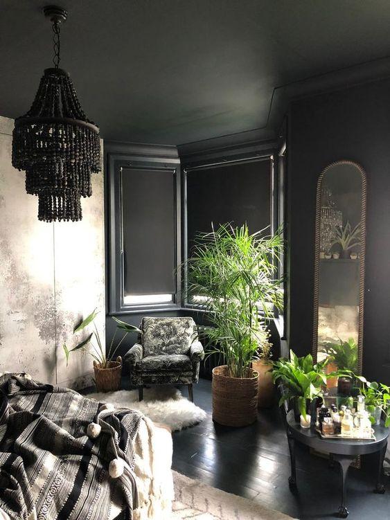 une chambre gothique moderne avec des murs lambrissés noirs, une armoire à imprimé abstrait, des meubles sombres, des plantes en pot et un lustre en perles noires