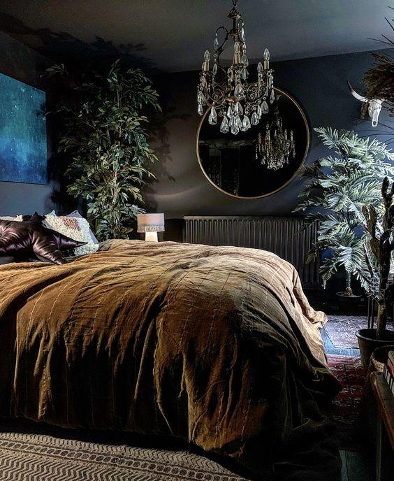 une chambre gothique moderne avec des murs noirs, une œuvre d'art lumineuse, un miroir rond, un lustre en cristal et des plantes en pot