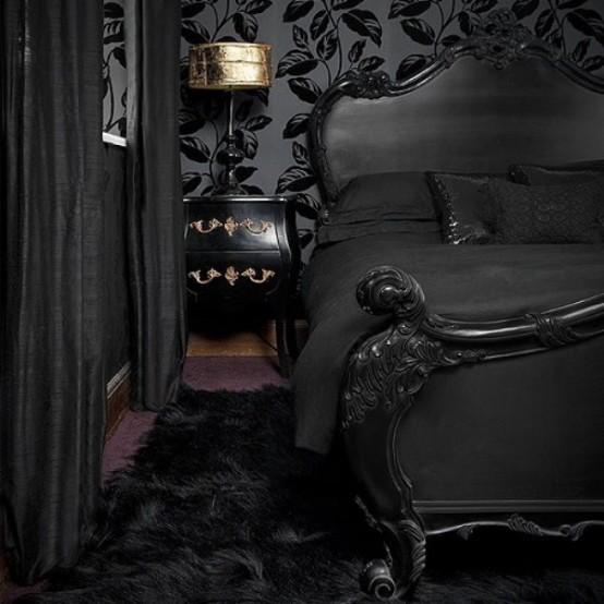 une chambre gothique raffinée avec du papier peint botanique noir, un lit noir sophistiqué, des tables de nuit noires et dorées, une lampe dorée et des textiles noirs