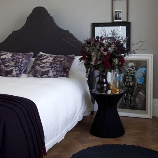 une chambre moderne avec une touche de gothique, un lit rembourré noir raffiné, une table de chevet noire, des œuvres d'art accrocheuses et un arrangement floral maussade