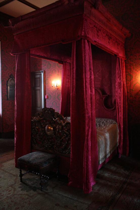 une chambre gothique vintage en cramoisi, avec du papier peint imprimé, un lit à baldaquin dans une couleur assortie et un mobilier exquis