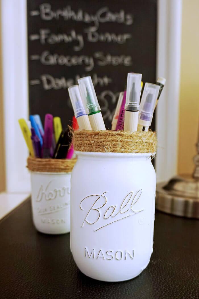 Les bocaux Mason contiennent des stylos et des peintures