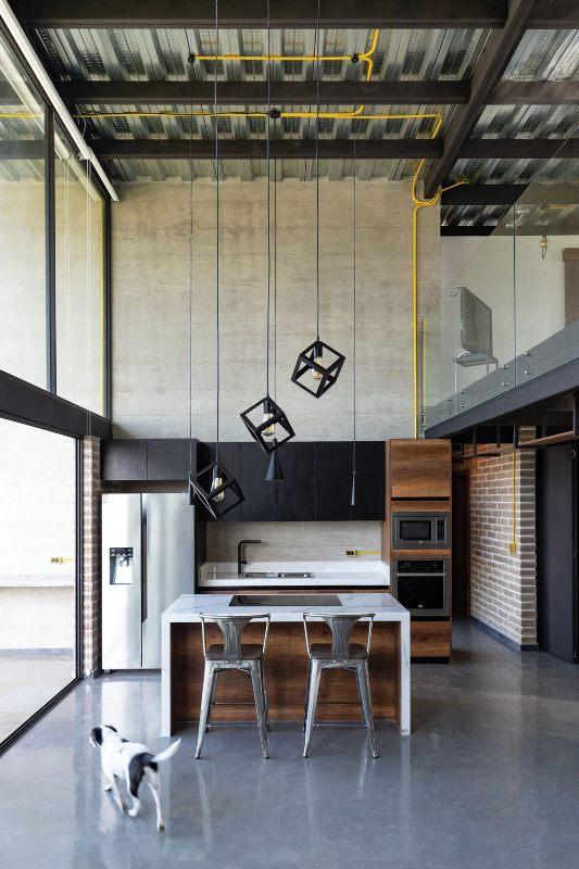 La cuisine est minimaliste, elle comprend des armoires supérieures noires, un îlot de cuisine en bois teinté et de magnifiques suspensions