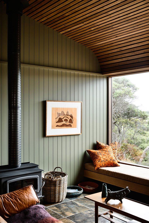Le salon dispose d'un plafond en dalle de bois, de murs en bois vert sauge et d'un siège de fenêtre confortable et d'un foyer