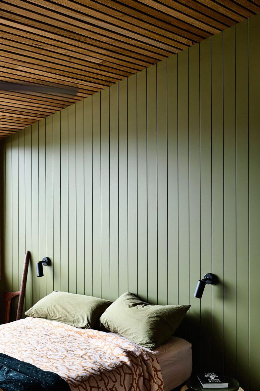 La chambre principale présente des murs vert sauge, un plafond en dalle de bois et des meubles confortables