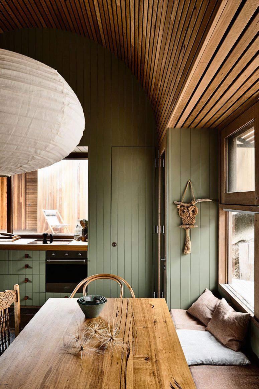 La cuisine et la salle à manger sont réunies en un seul espace également revêtu de bois vert sauge et avec des meubles assortis