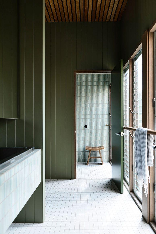 Une autre salle de bain présente des carreaux neutres et verts qui correspondent au bois vert sauge