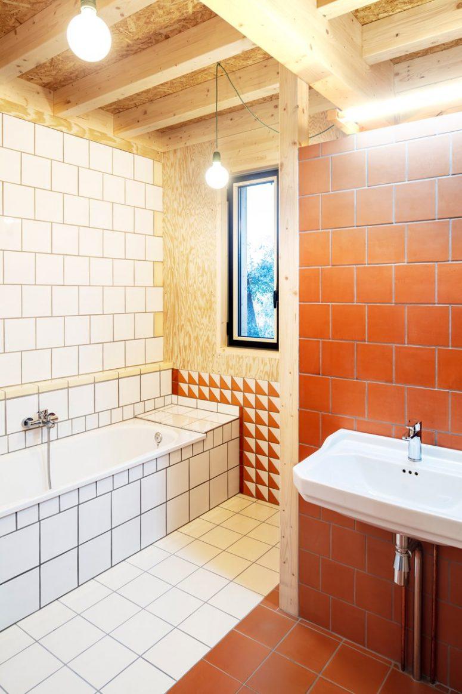 La salle de bain est faite avec des carreaux blancs et en terre cuite et du bois à nouveau
