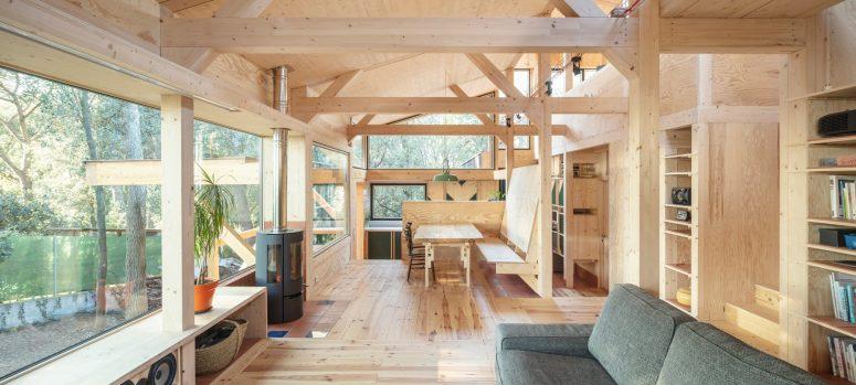 L'espace salle à manger comprend plusieurs fenêtres, un foyer et une table à manger avec des chaises et un banc