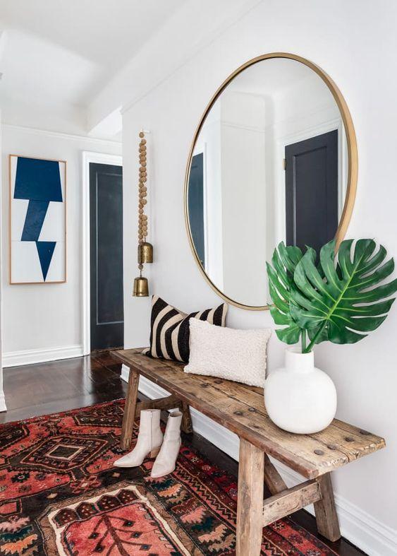 une entrée boho chic avec un banc en bois, un tapis boho, un miroir rond à cadre en bois et des cloches suspendues