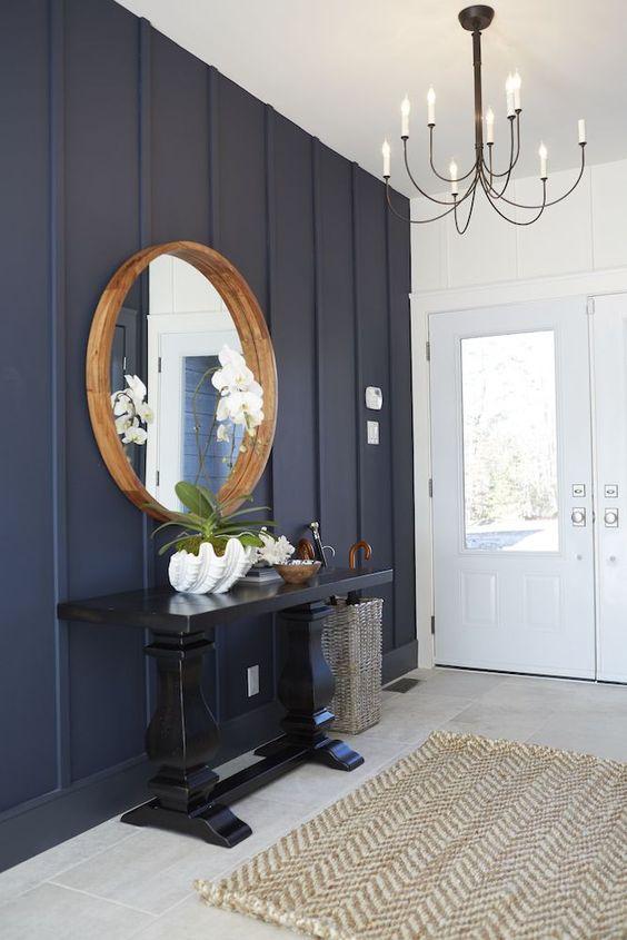 une entrée audacieuse avec un mur bleu marine, une table console noire et un miroir à cadre rond plus un lustre chic