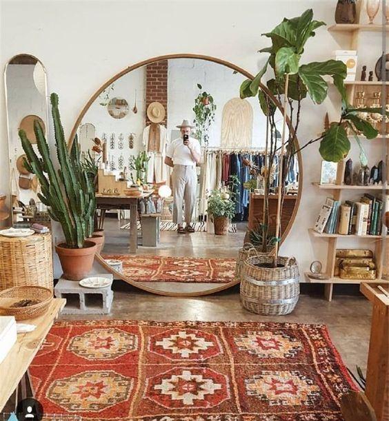 un salon bohème avec des meubles en bois et en osier, des plantes en pot, un tapis bohème et un miroir rond surdimensionné