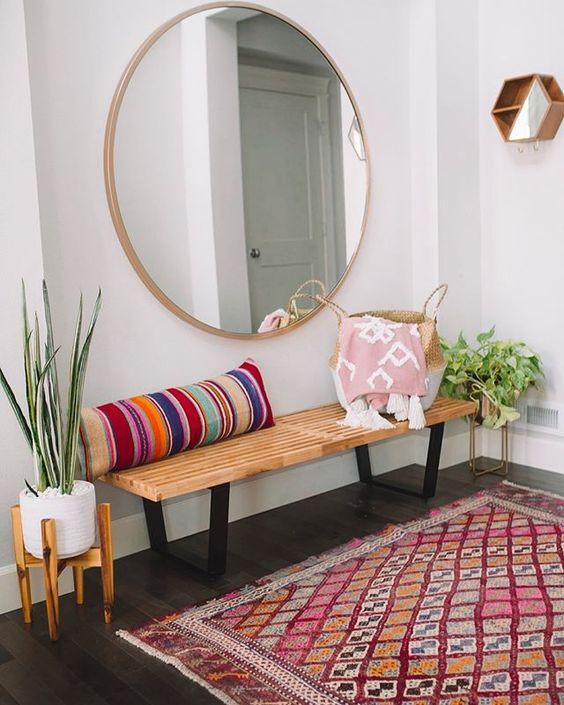 une entrée bohème colorée avec un banc en bois, un oreiller rayé, un miroir rond, un tapis lumineux et des plantes en pot