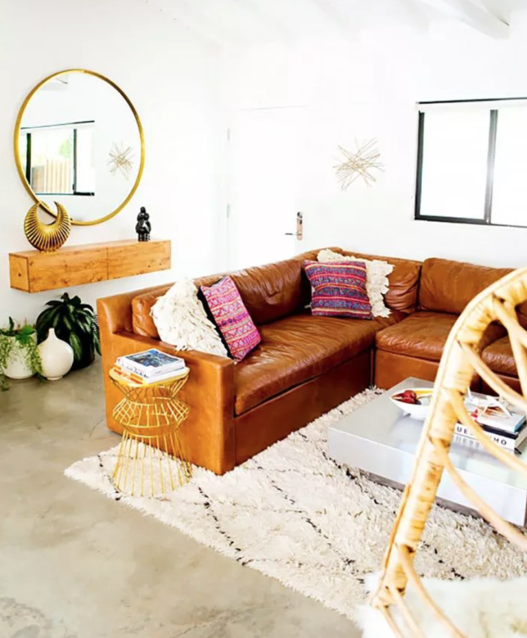 un salon bohème réalisé dans des tons neutres, avec un canapé en cuir marron, une coiffeuse flottante, un miroir rond encadré d'or et des touches de lune et d'étoiles