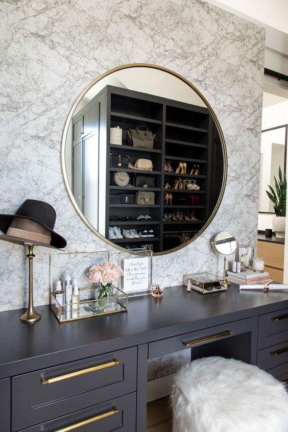 un placard chic avec un coin maquillage avec un mur en marbre, une vanité grise, un miroir à cadre doré et de nombreux accessoires