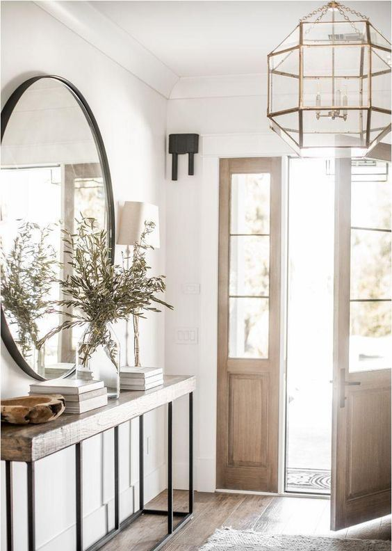 une entrée de ferme chic avec une console en bois et en métal, un lustre à facettes accrocheur et un miroir rond