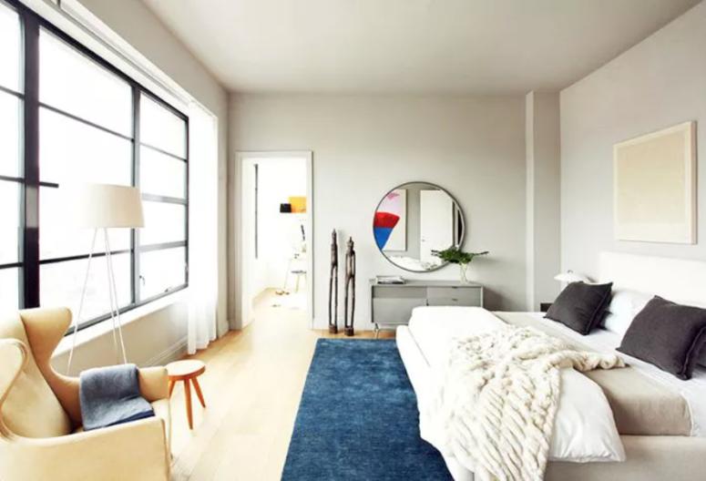 une belle chambre moderne neutre avec un lit rembourré confortable, une vnaity grise, des chaises et des tabourets confortables et un grand miroir rond