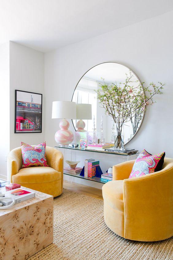 un salon moderne et coloré avec des murs neutres, des chaises jaunes, une table en dalle, une en acrylique et un miroir rond