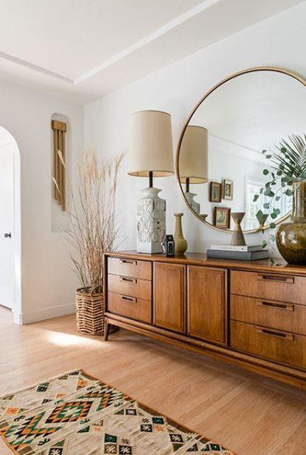 un salon moderne du milieu du siècle avec une coiffeuse en bois, une grande lampe, un miroir rond surdimensionné et quelques plantes
