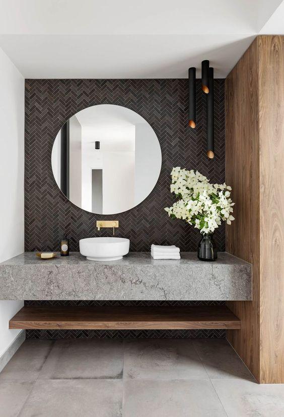 une magnifique salle de bain moderne avec un mur de carreaux gris, des lampes noires, une vanité en pierre grise et un miroir rond