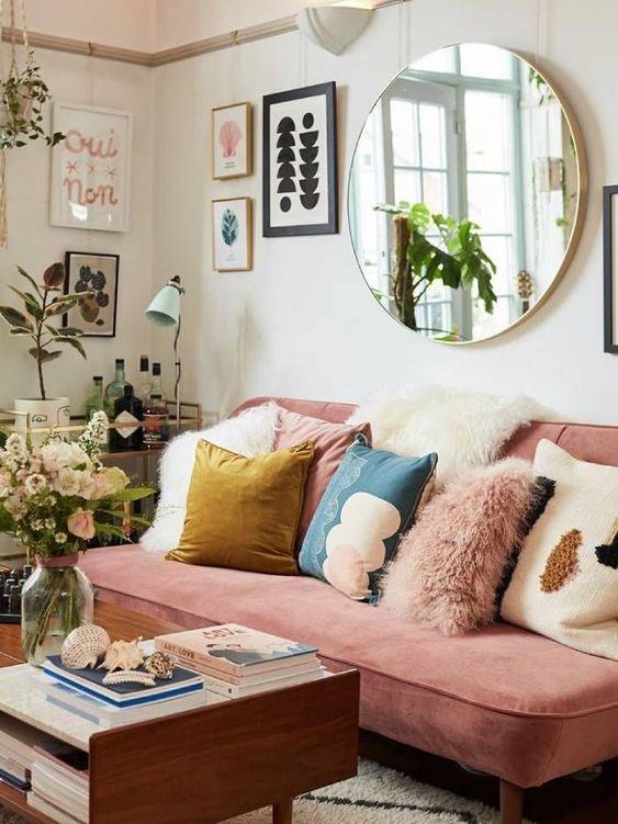 un salon éclectique coloré avec un canapé rose, des oreillers colorés, des plantes en pot, un mur de galerie et un miroir rond