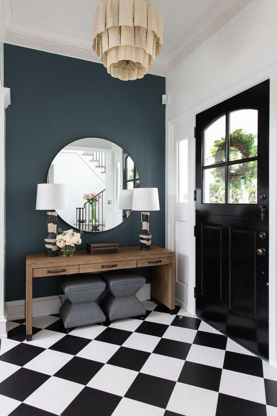 une entrée glam art déco avec une table console en bois, des tabourets gris, des lampes de base imprimées et un miroir rond