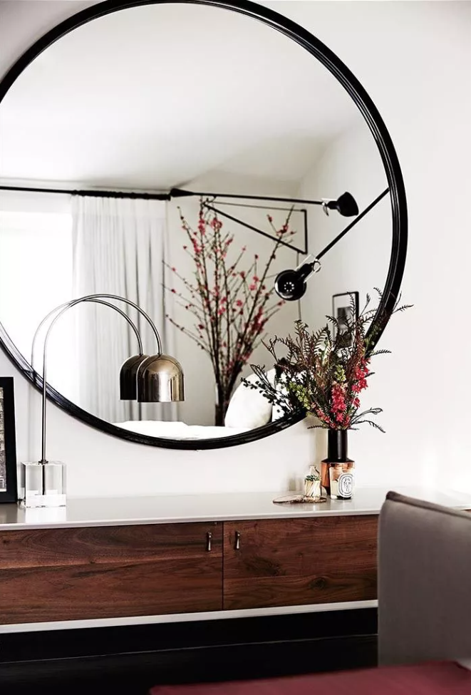 un salon raffiné avec des murs blancs, un mobilier sombre et vintage et un miroir rond surdimensionné qui remplit l'espace de lumière naturelle