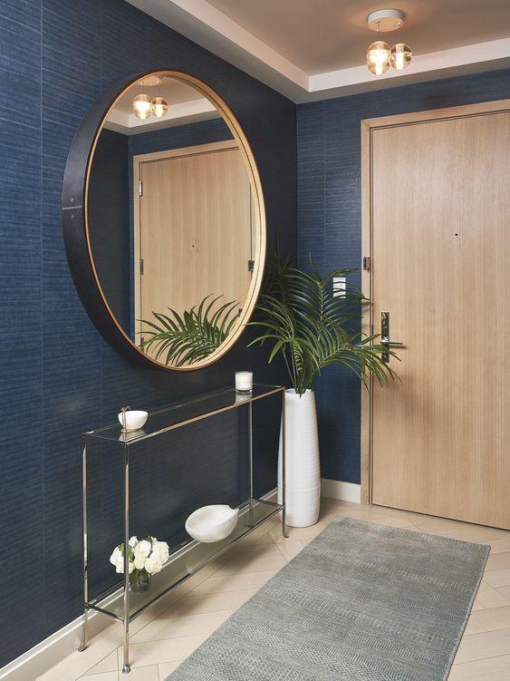 un foyer moderne et raffiné avec des murs bleu marine, une console en verre, un miroir rond à cadre noir et une plante dans un vase