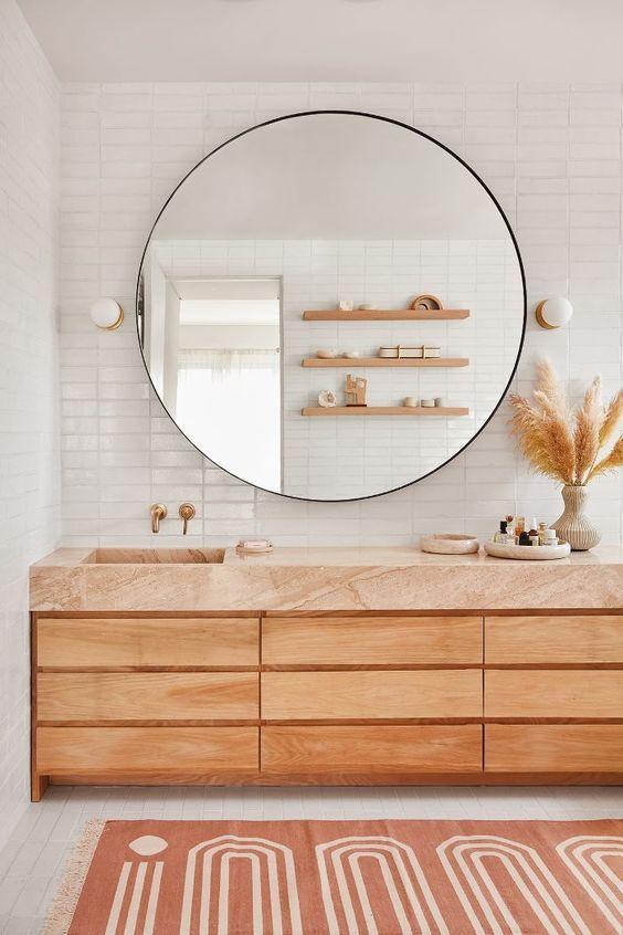 une salle de bain moderne et naturelle avec des carreaux blancs, une vanité en bois avec un dessus en terre cuite et un grand miroir rond dessus