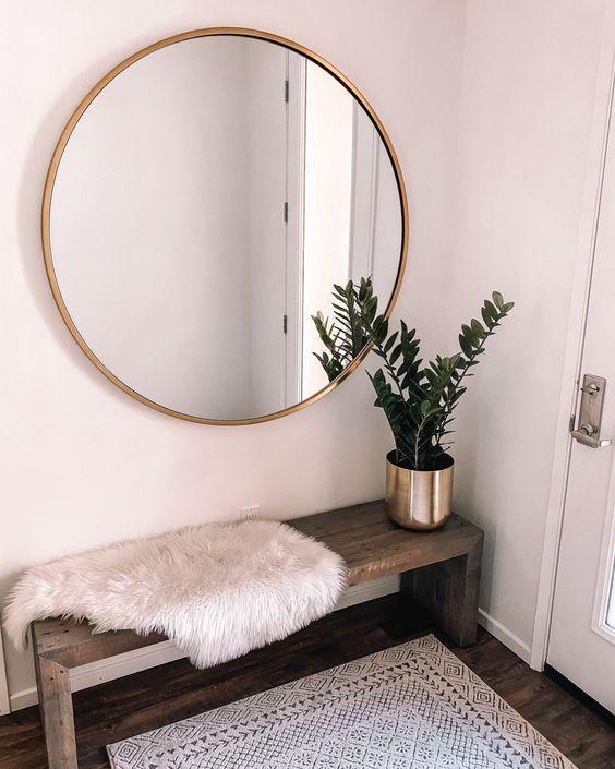 une entrée boho minimal avec un banc en bois, un tapis imprimé, une couverture en fausse fourrure et une plante en pot plus un miroir rond