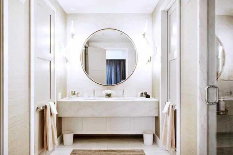 une salle de bain neutre revêtue de marbre blanc, avec des murs neutres et un grand miroir rond éclairé pour rendre l'espace encore plus lumineux
