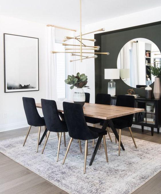 une salle à manger glamour moderne avec un mur d'accent gris, un grand miroir rond, un lustre accrocheur et des chaises noires