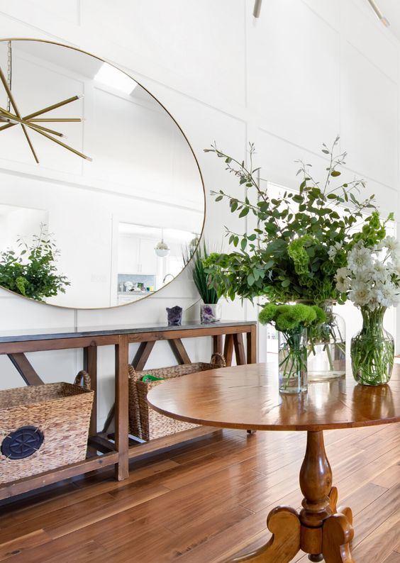 une entrée rustique avec une console et une table en bois, avec des paniers, un miroir rond surdimensionné et beaucoup de verdure