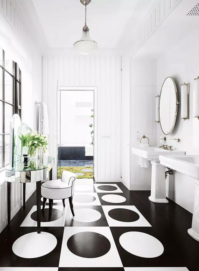 une salle de bains monochromatique raffinée avec des murs en lambris blancs, des lavabos blancs et un miroir surdimensionné à cadre blanc