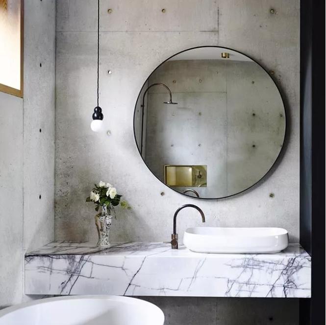 une salle de bain industrielle avec des murs en béton, un meuble-lavabo en marbre, un miroir rond surdimensionné et une suspension