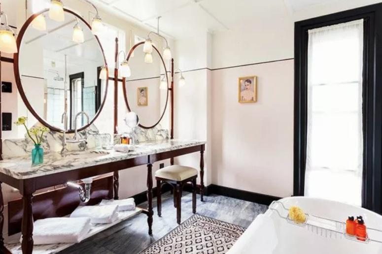 une salle de bain éclectique avec deux miroirs ronds surdimensionnés, une longue vanité vintage avec un plateau en marbre et un tapis imprimé