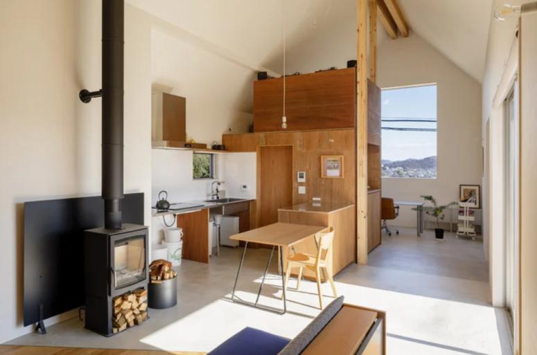 La cuisine est petite, elle est faite avec quelques armoires en contreplaqué, des ampoules suspendues, des comptoirs en pierre et une petite table