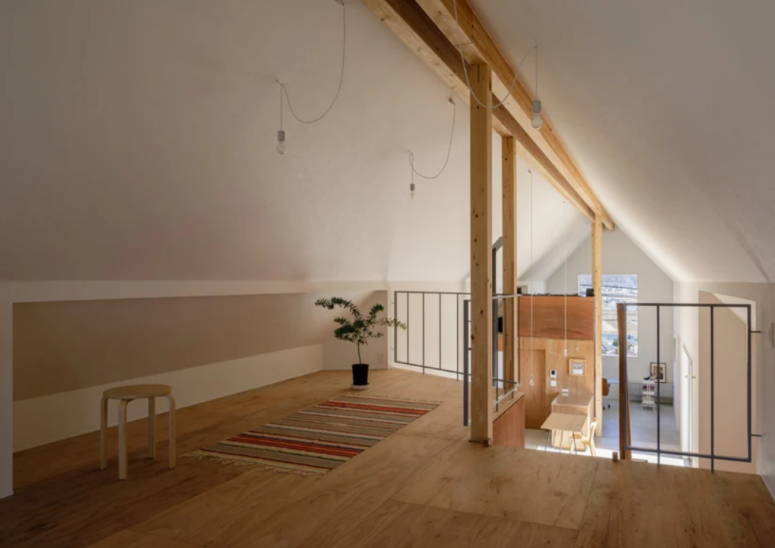 Il y a une chambre en mezzanine avec des ampoules, un tapis à rayures et des meubles confortables ici