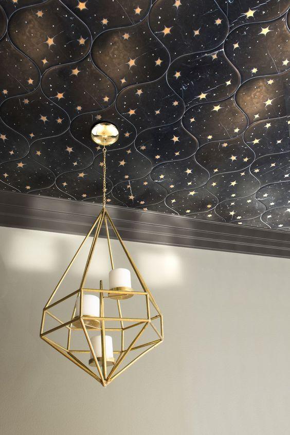 un beau plafond de carreaux étoilés noirs accentués d'un lustre à bougie d'or est une idée très audacieuse et chic