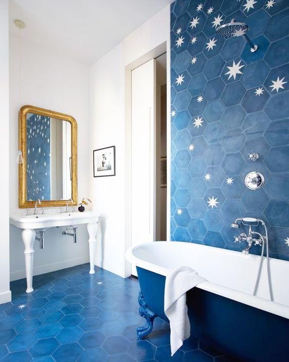 une salle de bain lumineuse revêtue de carreaux hexagonaux bleus et avec des étoiles imprimées dessus, une baignoire bleue et blanche et un lavabo blanc sur pied